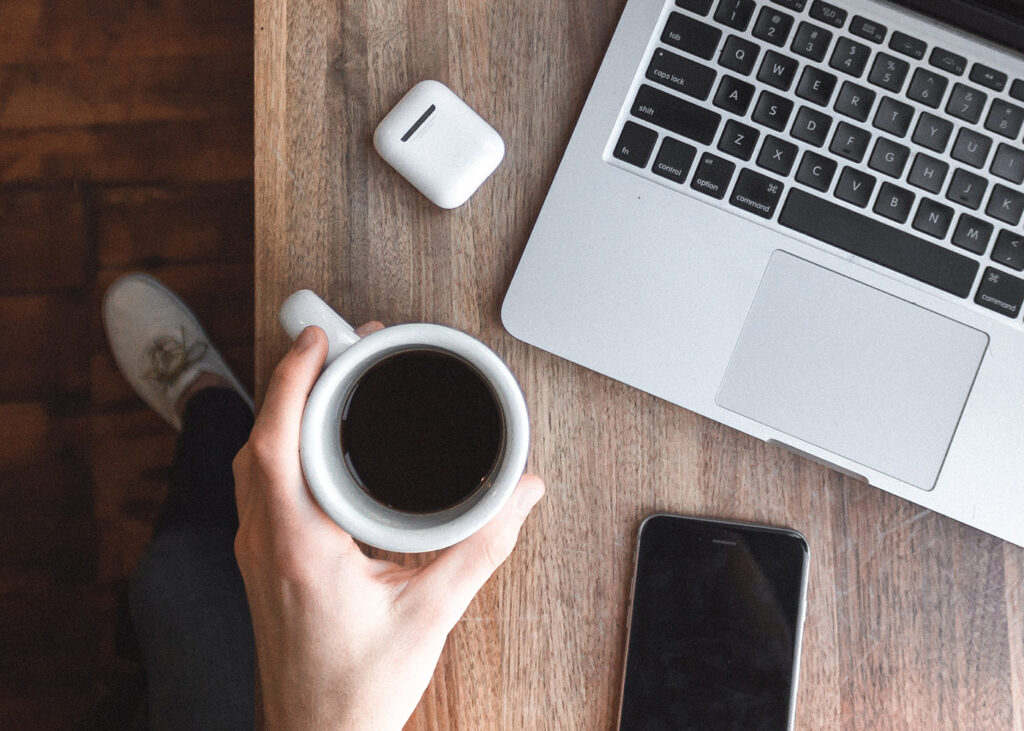 Person holding a cup of coffee with phone, laptop and earphones in shot